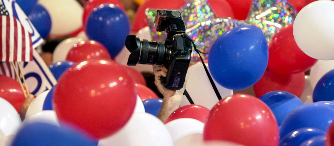 A photographer tries to negotiate a sea of balloons on the floor of the Democratic National Convention at the conclusion of the event in the Staples Center in Los Angeles, Thursday, Aug. 17, 2000. (AP Photo/David J. Phillip)